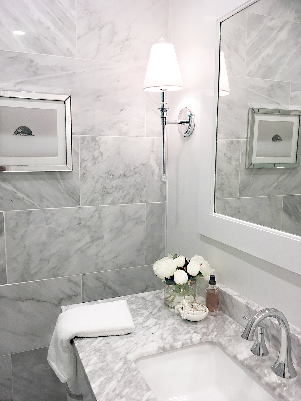 Classic marble ensuite with large format carrara marble tiles, herringbone marble floor and hex marble shower floor.